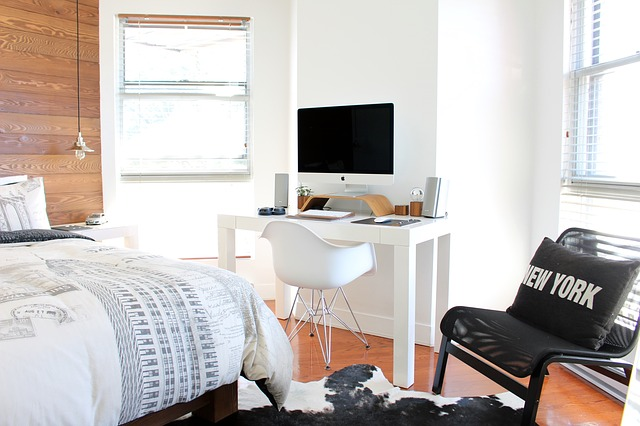Bedroom with white walls, a small desk, computer and a black chair by a window